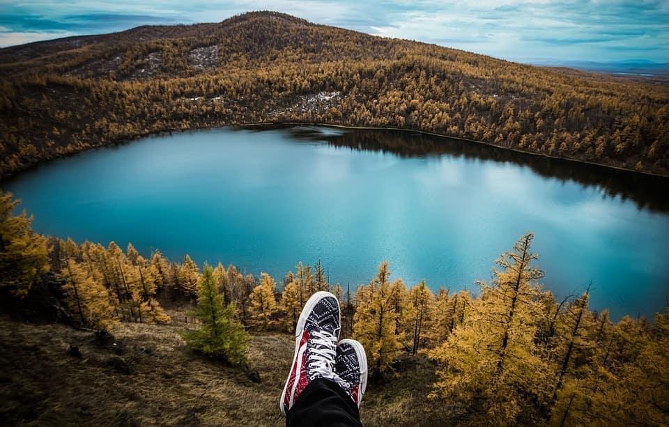 ragazzo in viaggio guarda panorama di lago