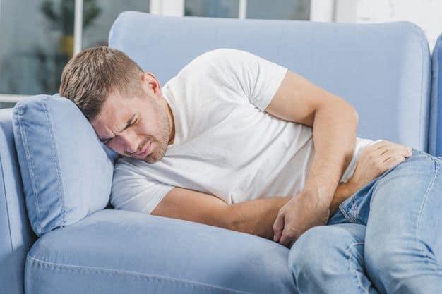 uomo con dolori sul divano