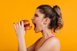 donna che mangia nervosamente un hamburger